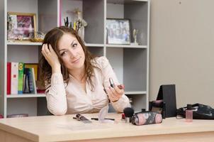 fille au bureau choisit le rouge à lèvres photo