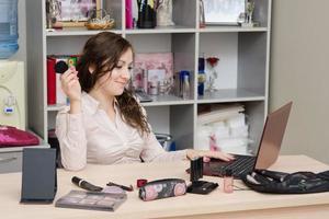 consultant cosmétiques heureux de travailler au bureau photo