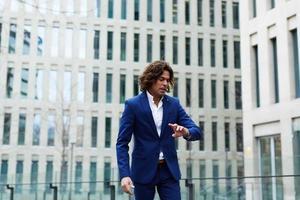Homme d'affaires prospère debout près d'un immeuble de bureaux photo