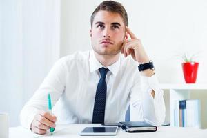 jeune bel homme travaillant dans son bureau. photo