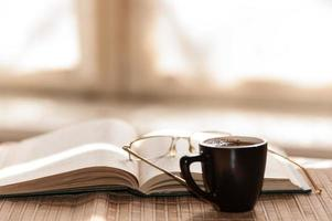 tasse de café, debout à côté d'un livre ouvert photo