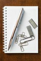 stylo sur le cahier avec les clips et les agrafes photo