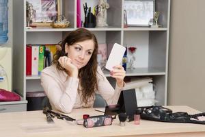 fille au bureau regarde le miroir photo