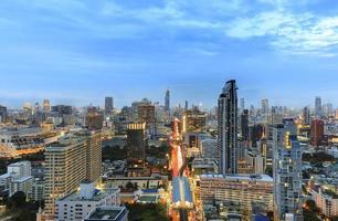 Immeuble de bureaux de Bangkok avec sky train au crépuscule photo