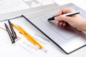 main féminine, utilisation, tablette graphique, sur, table, grand plan photo