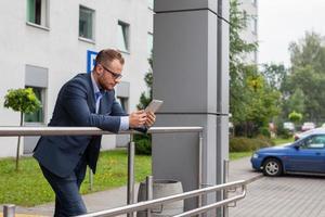 homme d'affaires caucasien à l'extérieur du bureau à l'aide de tablet pc blanc. photo