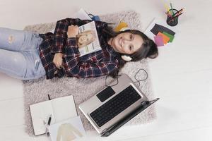 blogueuse occasionnelle montrant un magazine dans son bureau de mode. photo