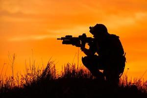 silhouette de soldat militaire ou officier avec des armes au coucher du soleil photo
