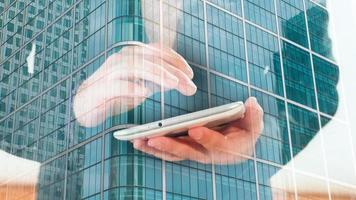 double exposition, homme d'affaires à l'aide de tablette et immeuble de bureaux de Londres
