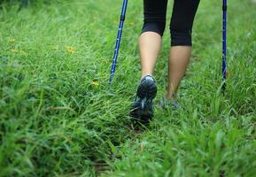 jambes de randonnée dans l'herbe verte photo