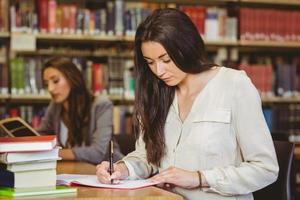 concentration jolie étudiante brune écrit dans le bloc-notes photo