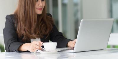 Asie femme au café avec ordinateur portable et café, concept d'entreprise photo