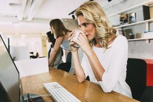 belle femme d'affaires, boire du thé pour rester alerte photo