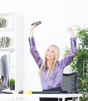 Jeune femme d'affaires blonde réussie, geste de victoire photo