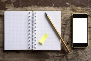 téléphone et bloc-notes sur table en bois photo