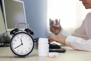 Homme d'affaires asiatique fatigué et malade, faire des heures supplémentaires avec des médicaments photo