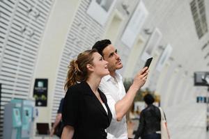Les jeunes voyageurs d'affaires homme femme station publique à la recherche d'horaire