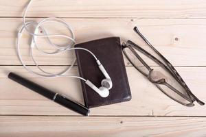 portefeuille marron, lunettes, écouteurs, stylo