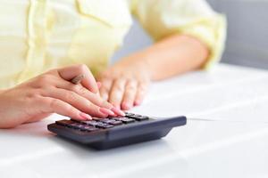 mains de femme avec une calculatrice photo