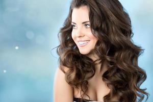 femme souriante aux cheveux longs sur fond bleu.