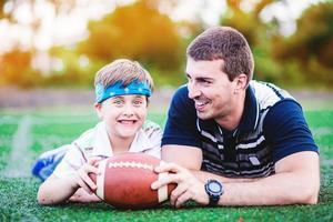 père et fils jouent au football dans le parc photo