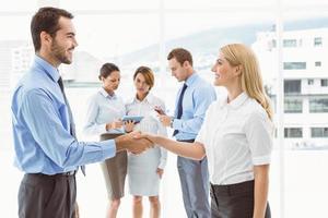 cadres se serrant la main avec des collègues derrière photo