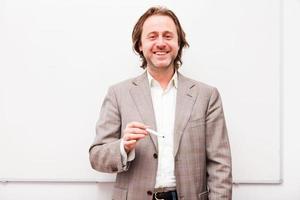 homme d'affaires cheveux longs debout devant le tableau blanc. photo