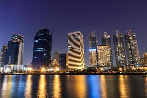 ville du centre-ville dans la nuit avec la réflexion du bâtiment dans la rivière. photo