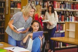 étudiants utilisant une tablette numérique avec leurs camarades de classe derrière photo