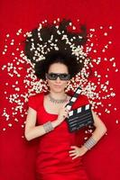 fille cool avec des lunettes de cinéma 3d, du pop-corn et un clap de réalisateur photo