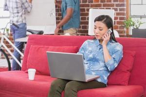 femme décontractée à l'aide d'un ordinateur portable et d'un téléphone portable sur un canapé photo