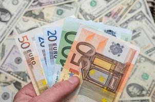billets d'euro au-dessus de fond de dollars photo