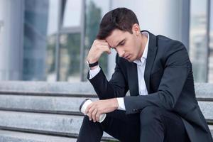 séduisant jeune homme d'affaires s'inquiète pour son travail photo