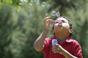 jeune garçon soufflant des bulles à l'extérieur dans le parc