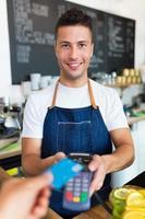 homme tenant le lecteur de carte de crédit au café