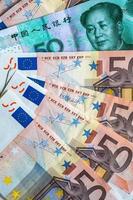 cinquante billets en euros et cinquante billets en yuans photo