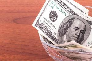Billets en dollars dans un bol en verre photo