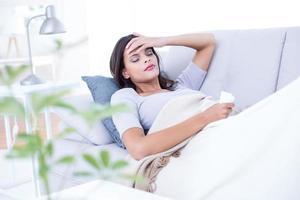 brune malade allongée sur le canapé photo