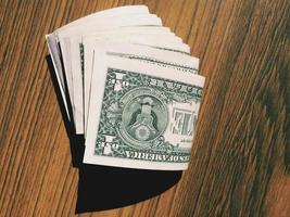 billets d'un dollar américain sur un fond en bois. photo