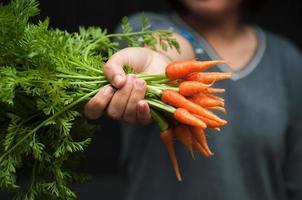 femme offrant des bébés carottes. photo