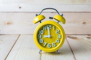 réveil jaune sur fond de bois photo