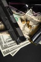pistolet avec balle sur les billets en dollars américains photo