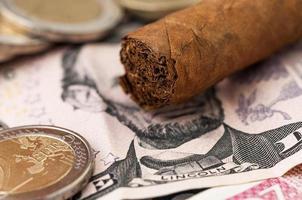 billet de cinq dollars d'argent et cigare cubain photo