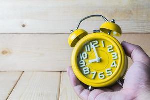 main tenir réveil jaune sur fond de bois photo