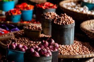 noix et oignons pelés dans de petits seaux au marché local