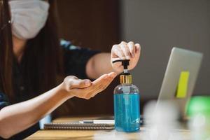 une femme asiatique à l'aide de désinfectant pour les mains pendant le travail de quart photo