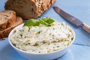beurre aux herbes dans un bol sur bois bleu photo