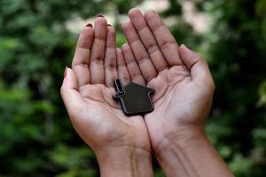 mains de femme tenant la maison verte photo