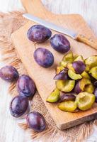 tranches de prunes mûres fraîches sur une planche à découper en bois photo