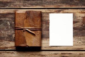 Fermer le cahier Leaher avec une feuille de papier d'en haut photo